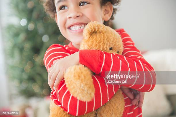 Mixed race boy hugging teddy bear at Christmas
