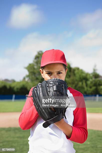 mixed race boy in baseball uniform holding glove and concentrating - 投手 ストックフォトと画像