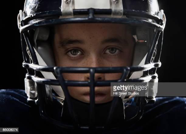 Mixed race boy in football uniform