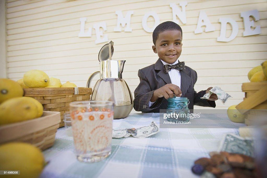 Mixed race boy in suit selling lemonade : Stock Photo