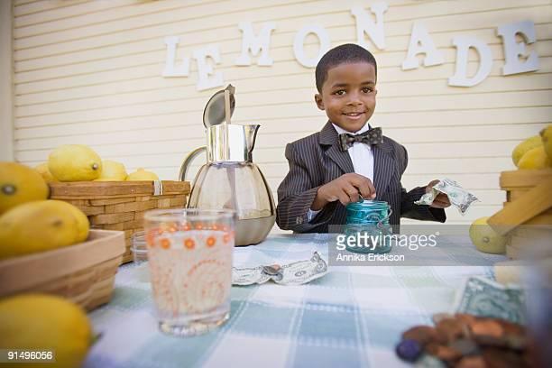 Mixed race boy in suit selling lemonade