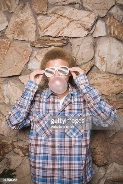 Mixed race boy in sunglasses chewing bubble gum