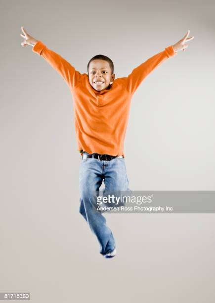 Mixed Race boy jumping in air