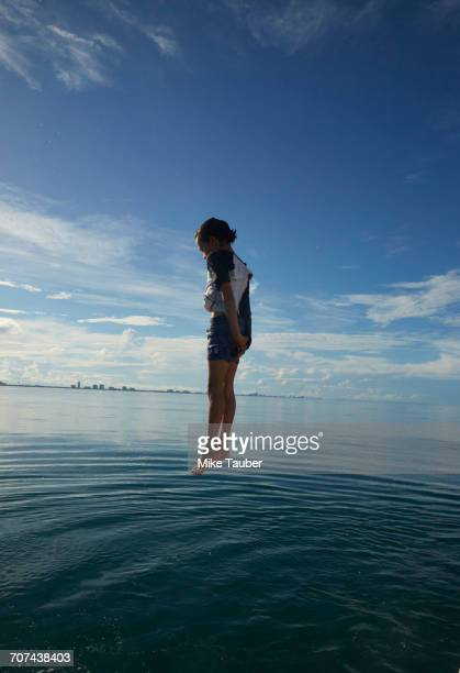 mixed race boy jumping into ocean - hovering stock pictures, royalty-free photos & images