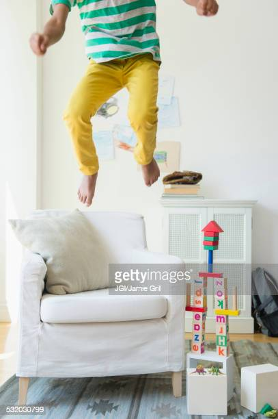 Mixed race boy jumping on armchair in living room