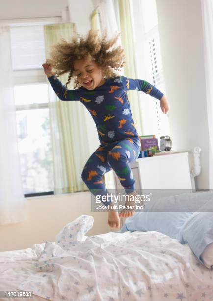 Mixed race boy jumping on bed