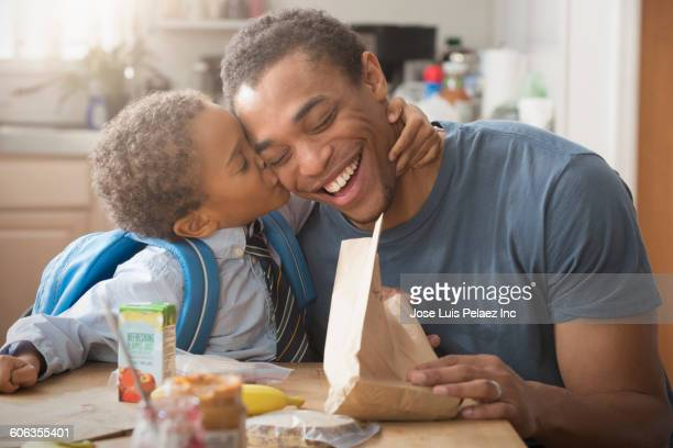 Mixed race boy kissing father in kitchen