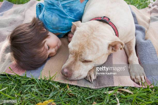 Mixed race boy laying on blanket with dog