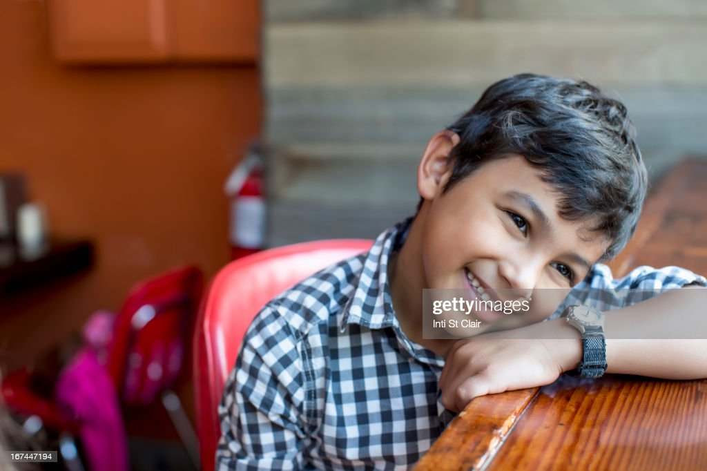 Mixed race boy leaning on bar : Stock Photo