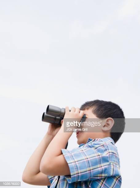 Mixed race boy looking through binoculars