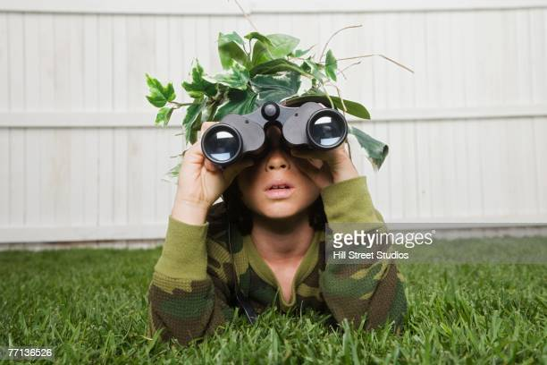 mixed race boy looking through binoculars - camouflage clothing stock pictures, royalty-free photos & images