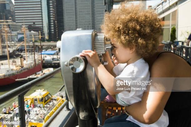 Mixed race boy looking through telescope