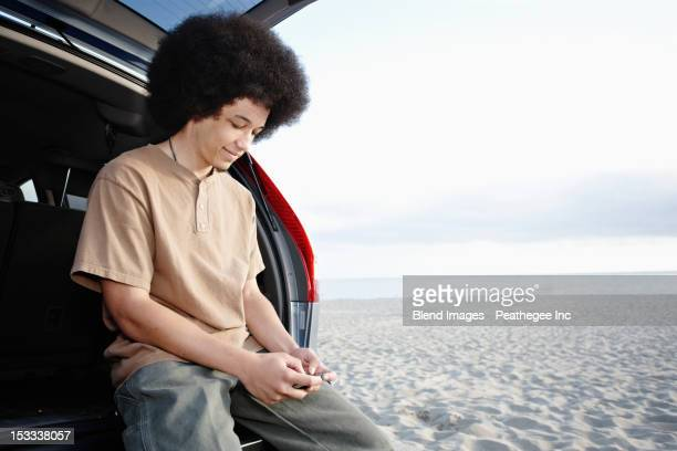 Mixed race boy on beach test messaging on cell phone