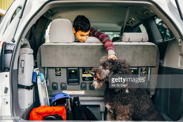 Mixed race boy petting dog in car hatch