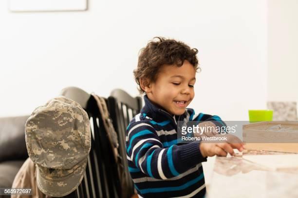mixed race boy playing at counter near camouflage cap - roberto ricciuti foto e immagini stock
