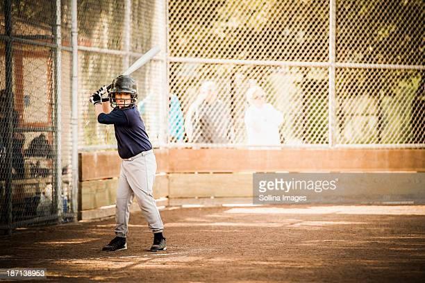 Mixed race boy playing baseball in field