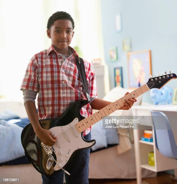 Mixed race boy playing electric guitar