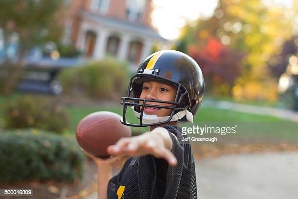 Mixed race boy playing football outdoors