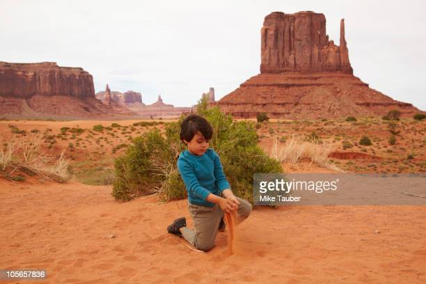 Mixed race boy playing in dirt in Monument Valley