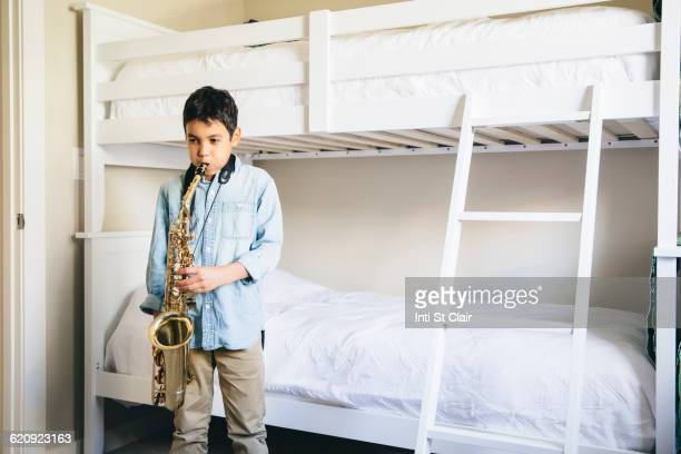 Mixed race boy playing saxophone in bedroom