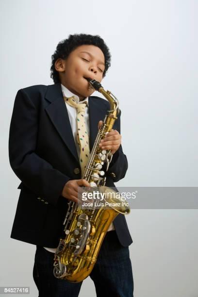 Mixed race boy playing saxophone