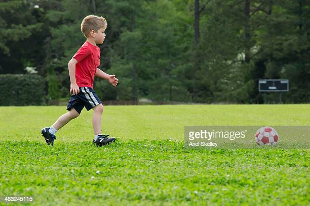 Mixed race boy playing soccer