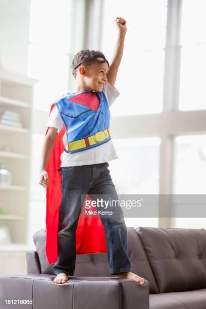 Mixed race boy playing superhero