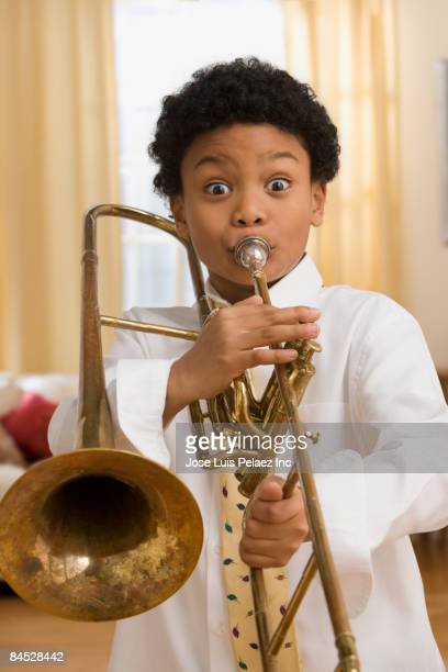Mixed race boy playing trombone