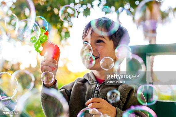 Mixed race boy playing with bubbles outdoors