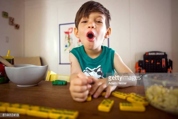Mixed race boy playing with dominoes at kitchen table