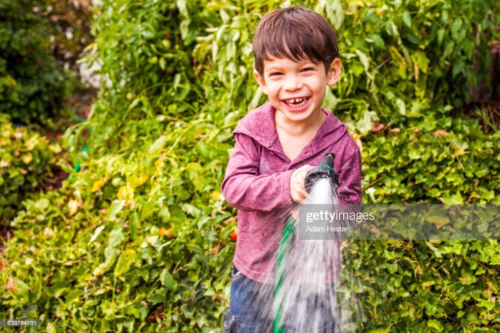 Mixed race boy playing with hose in garden : Foto stock