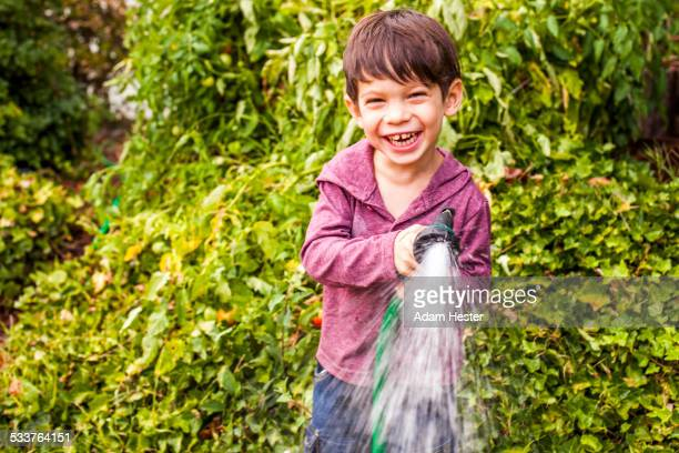 Mixed race boy playing with hose in garden