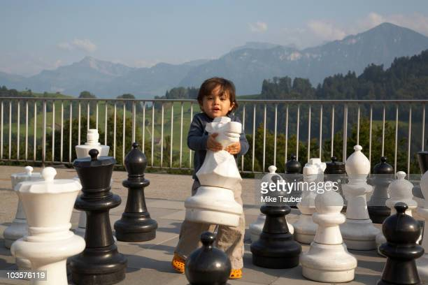 mixed race boy playing with large chess pieces - big mike stock pictures, royalty-free photos & images