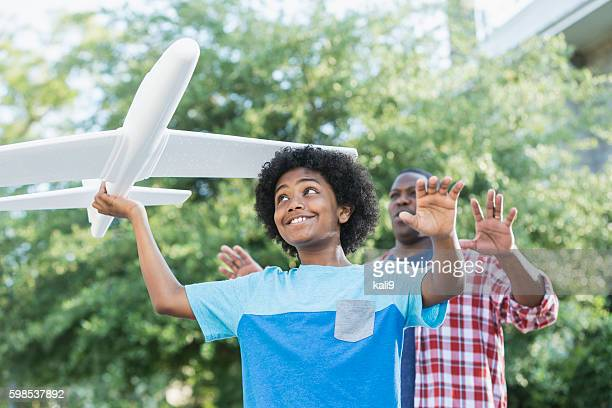 Mixed race boy playing with toy plane, father behind