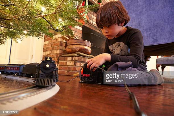 Mixed race boy playing with train under Christmas tree