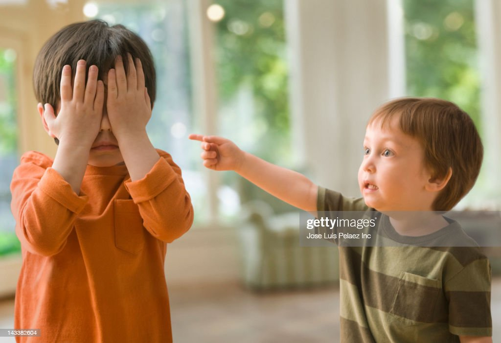 Mixed race boy pointing at brother who's covering his eyes : Stock Photo