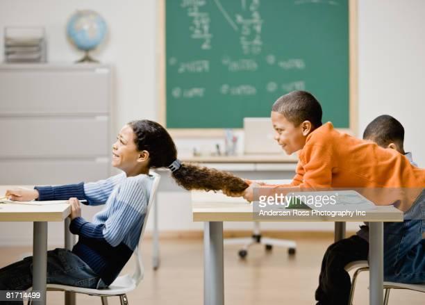 Mixed Race boy pulling girl's hair in school