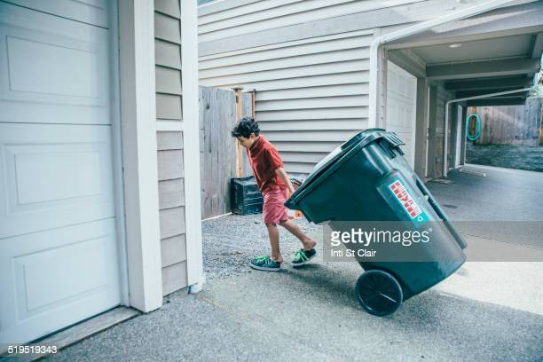 Mixed race boy pulling trash can in driveway