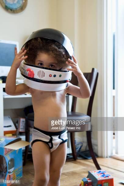 Mixed race boy putting on astronaut helmet