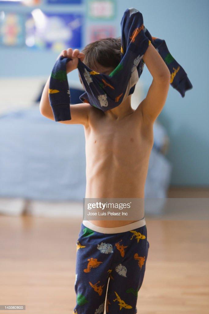 Mixed race boy putting on pajamas : Stock Photo