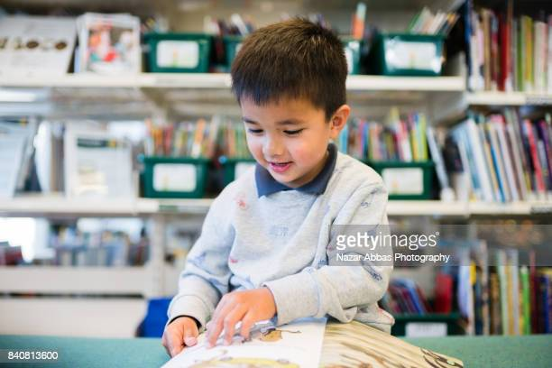 Mixed race boy reading book in library.