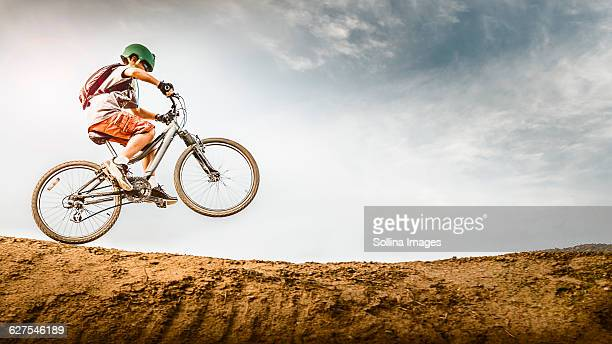Mixed race boy riding dirt bike on track