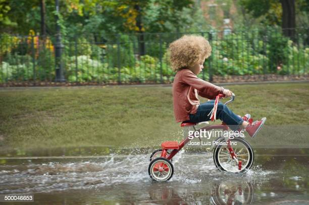 mixed race boy riding tricycle in park - tricycle stock pictures, royalty-free photos & images