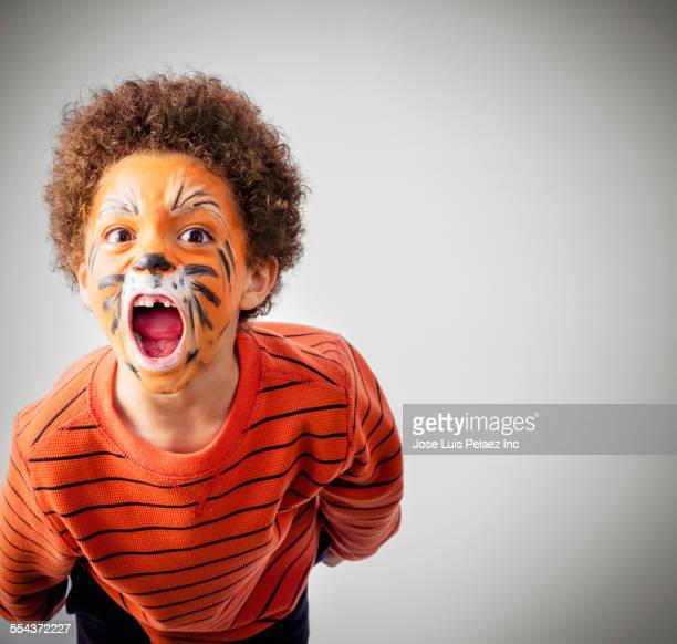 mixed race boy roaring in tiger face paint - halloween kids stock photos and pictures