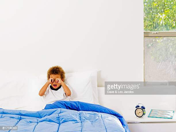 Mixed Race boy rubbing eyes in bed