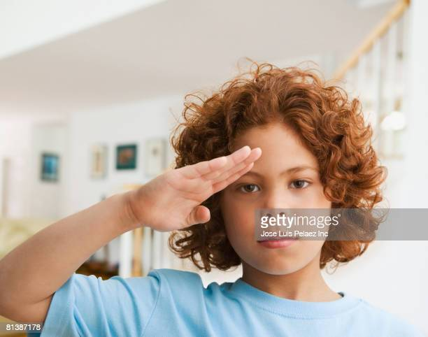 mixed race boy saluting - saluting stock pictures, royalty-free photos & images