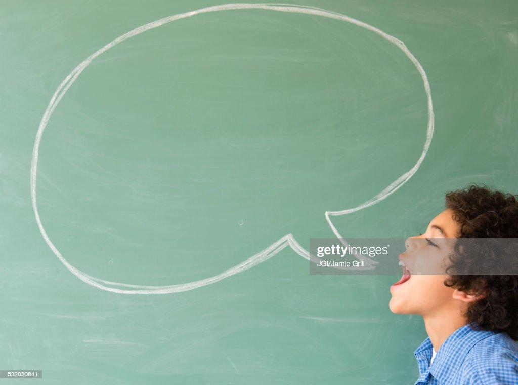 Mixed race boy shouting into speech bubble on chalkboard : Stock Photo