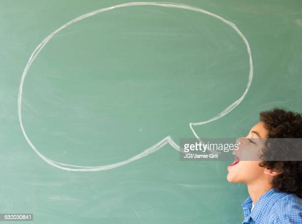 mixed race boy shouting into speech bubble on chalkboard - blackboard visual aid stock pictures, royalty-free photos & images