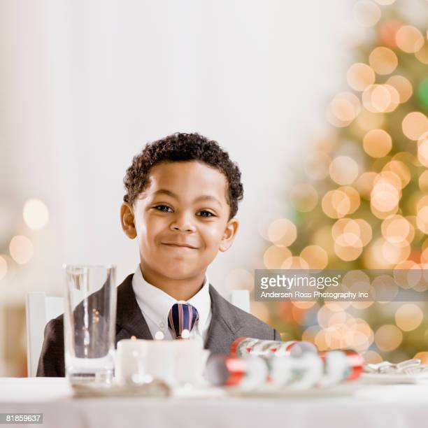 Mixed Race boy sitting at holiday table