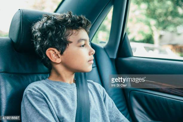 Mixed race boy sitting in car back seat